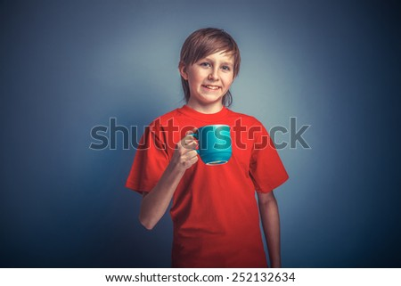 European -looking  boy of ten years  holding a mug on a gray background retro