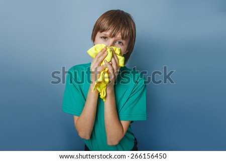 European-looking boy of ten years is ill, a handkerchief, a runny nose on a gray  background - stock photo