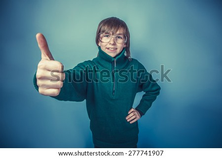 European -looking boy of ten years showing thumbs up on blue background instagram effect style