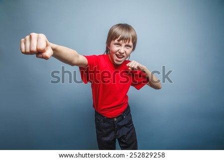 European-looking boy of ten years shows a fist, anger, danger, mouth open on a gray background - stock photo