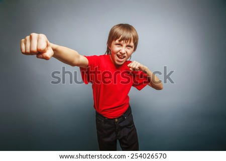 European-looking boy of ten years shows a fist, anger, danger, mouth open on a gray background cross process - stock photo