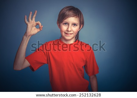 European-looking boy of ten years thumbs up gesture okay on a gray background retro - stock photo