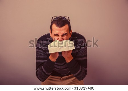 European-looking male of about thirty brunet blowing his nose into a handkerchief on a gray background, runny nose retro - stock photo