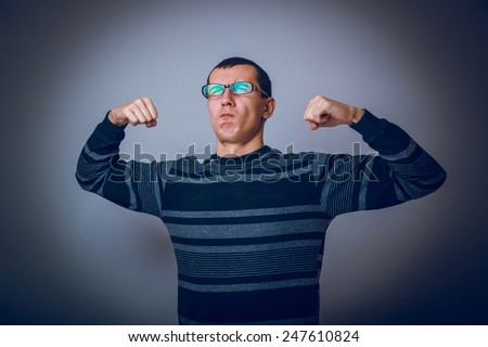 European-looking male of about thirty brunet shows muscle strength cross process - stock photo