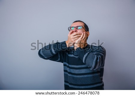 European-looking male of about thirty shut his mouth yawns hands on a gray background - stock photo