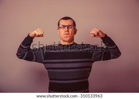 European-looking man of 30 years in glasses shows muscles retro