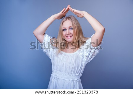 European-looking woman thirty years his hands over his head, a gesture I have in the house on a gray background - stock photo