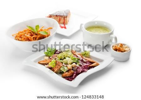 European Lunch - Caesar Salad with Chicken Breast, Veggie Cream Soup, Spaghetti Bolognese and Dessert - stock photo