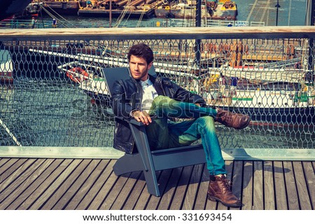 European Man traveling in New York. Dressing in black leather jacket, blue jeans, brown boot shoes,  a young guy with beard, sitting on chair on deck, crossing legs, relaxing. Boats on background.  - stock photo