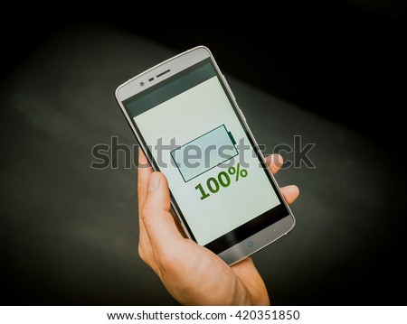 European mans hand holding new silver smartphone on the black background. Full charge is on the screen,  - stock photo