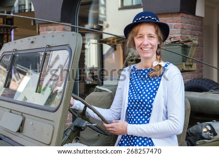 European middle aged woman steering green military jeep on liberation party. The caucasian woman wears a blue dress and a hat. She's looking at the camera - stock photo