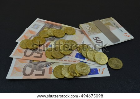 European money on a black table. Euros and russian rubles on a table. Money and clips for money. Coins and banknotes on a table with black background