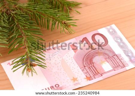 european money ten euro and green eve on wooden background - stock photo