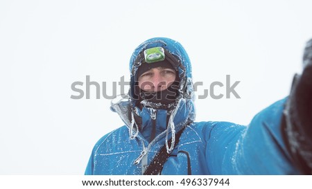 European person does Selfie portrait on white background. Hoarfrost on a blue jacket. Frosty winter day in the cloudy and cold weather. Adventure tourist at a mountain hike