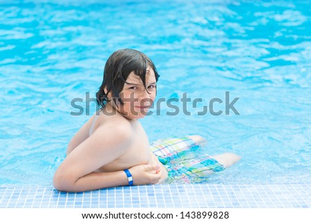 European school-age boy sitting on the edge of the pool in a blue bathing suit and looking at the camera