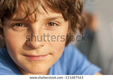 European school-age boy with brown eyes looking directly at the camera, close-up