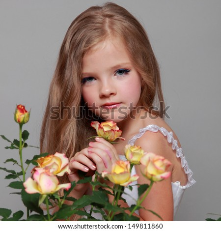 European smiling little girl in a white dress with long hair holds a healthy fresh roses with green leaves on Beauty and Fashion