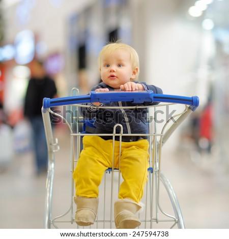 European toddler boy sitting in the shopping cart - stock photo