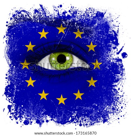 European Union flag painted on face with green eye - stock photo