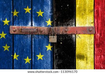 European Union flag with the Belgian flag on the background of old locked doors - stock photo
