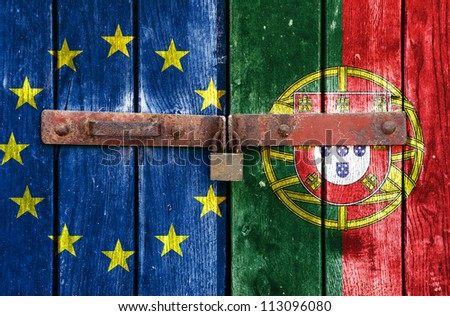 European Union flag with the Portugal flag on the background of old locked doors - stock photo
