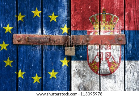 European Union flag with the Serbian flag on the background of old locked doors - stock photo