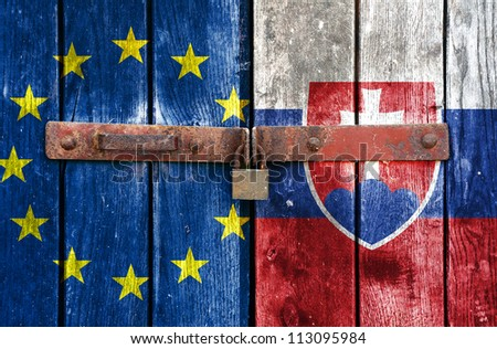 European Union flag with the Slovakia flag on the background of old locked doors - stock photo