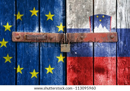 European Union flag with the Slovenian flag on the background of old locked doors