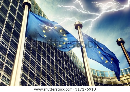 European Union flags on dark thunderstorm sky background - stock photo