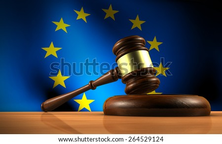 European Union law, legislation and parliament concept with a 3d rendering of a gavel on a wooden desktop and the EU flag on background. - stock photo