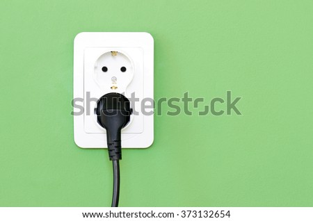 European white electrical outlet socket and black cable plugged in isolated on green wall - stock photo