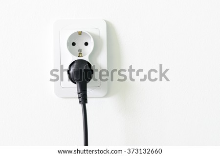 European white electrical outlet socket and black cable plugged in isolated on white wall - stock photo