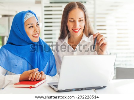 European woman and asian muslim woman working together on same project - stock photo