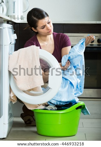 european woman with musty towels after laundry at home
