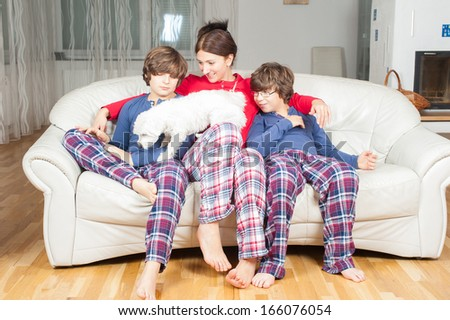 European woman with two sons and a white dog in pajamas on the couch - stock photo