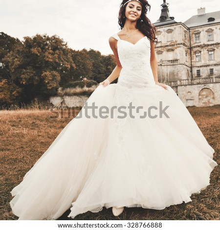 European young beautiful bride next to ancient castle.