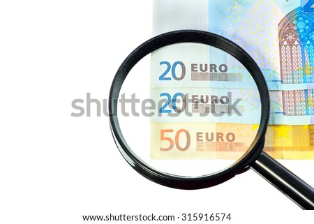 Euros banknote under a magnifying glass is being inspected on white background - stock photo