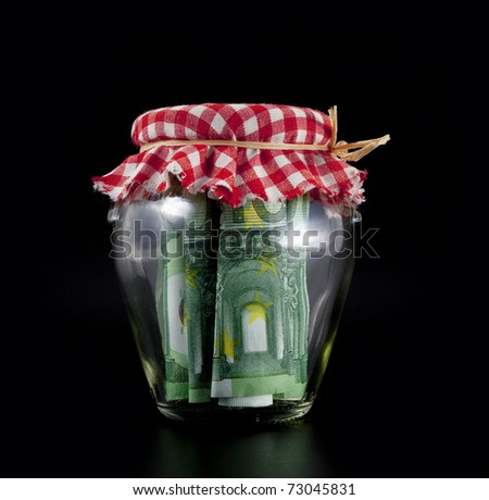 Euros in a jar left for the future, on a black background. - stock photo