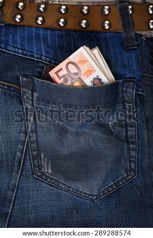Euros sticking out of a jeans pocket. - stock photo