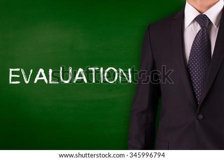 EVALUATION on Blackboard with businessman - stock photo