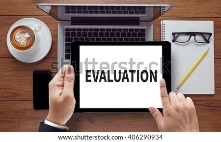 EVALUATION, on the tablet pc screen held by businessman hands - online, top view - stock photo