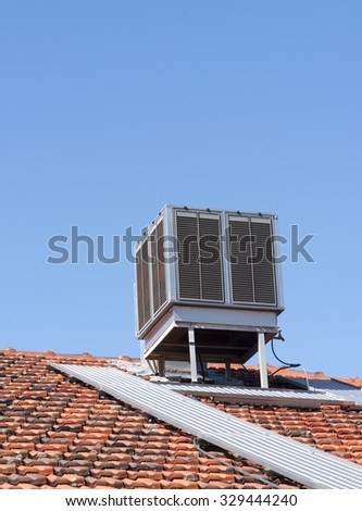 Evaporative air conditioner on top of tiled roof - stock photo
