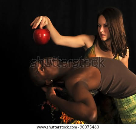Eve tempting Adam with and apple on a black background in the garden of eden. - stock photo