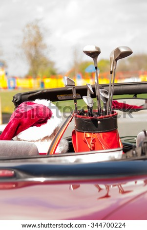 Even the jolly old elf loves a day on the links. Santa driving a red convertible to the golf course for a relaxing day of golf. - stock photo