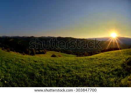 Evening and sunset on mountain hills of Simon village. Bran. - stock photo