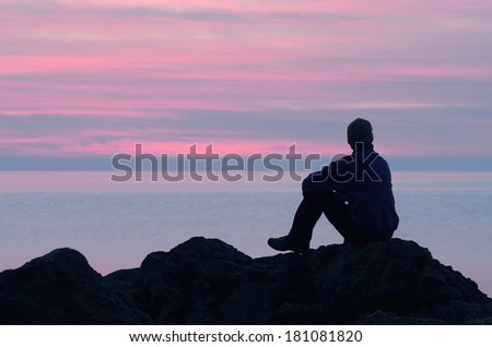 Evening at the seaside. Guy sits on a rock by the sea and looking at sunset