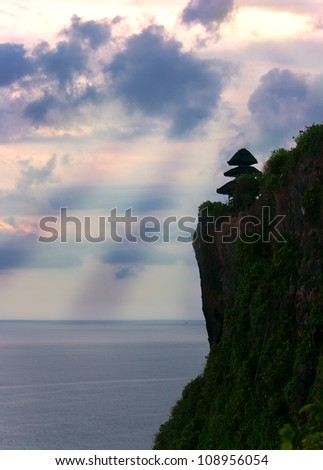 Evening at Uluwatu temple on Baly. Sunbeams through the clouds. - stock photo