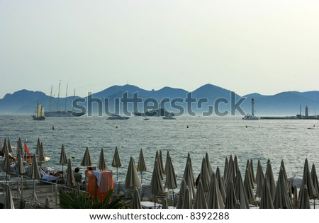Evening beach with closed umbrellas in Cannes. View on the sea with yachts, lighthouse, and horizon ending up with hill silhouettes - stock photo