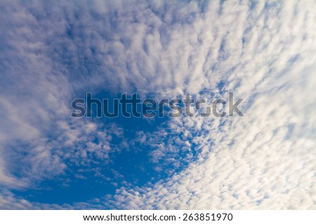 Evening clouds in a spring sky rippled with wind - stock photo