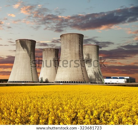 Evening colored view of nuclear power plant Dukovany with golden glowering field of rapeseed - Czech Republic - two possibility for production of energy